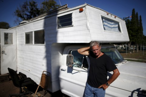 """Nathan Allen, 65, poses for a portrait in front of the motorhome where he sleeps in a homeless RV and tent encampment near LAX airport in Los Angeles, California, United States, October 26, 2015. Allen lost his job as a handyman, and so couldn't afford to pay the rent for his apartment. Los Angeles is grappling with a massive homelessness problem, as forecasted El Nino downpours threaten to add to the misery of thousands of people who sleep on the streets. Mayor Eric Garcetti has proposed spending $100 million to combat the problem in the sprawling metropolis but stopped short of declaring a state of emergency. REUTERS/Lucy Nicholson PICTURE 16 OF 17 - SEARCH """"NICHOLSON MOTORHOME"""" FOR ALL IMAGES - GF10000270563"""