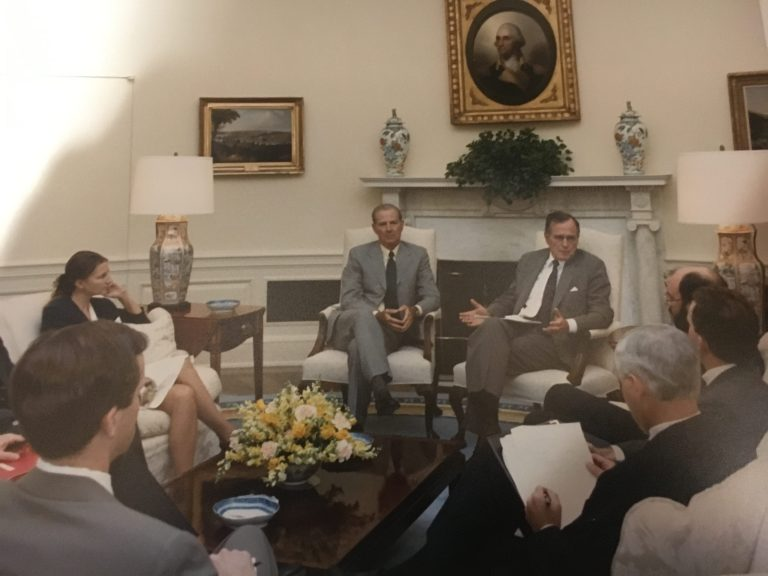 President George H.W. Bush leads a discussion about Iraqi President Saddam Hussein in the Oval Office in the fall of 1990. CIA Officer Bruce Riedel is responding to the president.