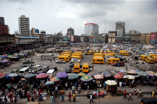 People walk past roadside stalls with umbrellas in the central business district, near Marina in Lagos, Nigeria December 13, 2016.REUTERS/Akintunde Akinleye - RC119A3413E0
