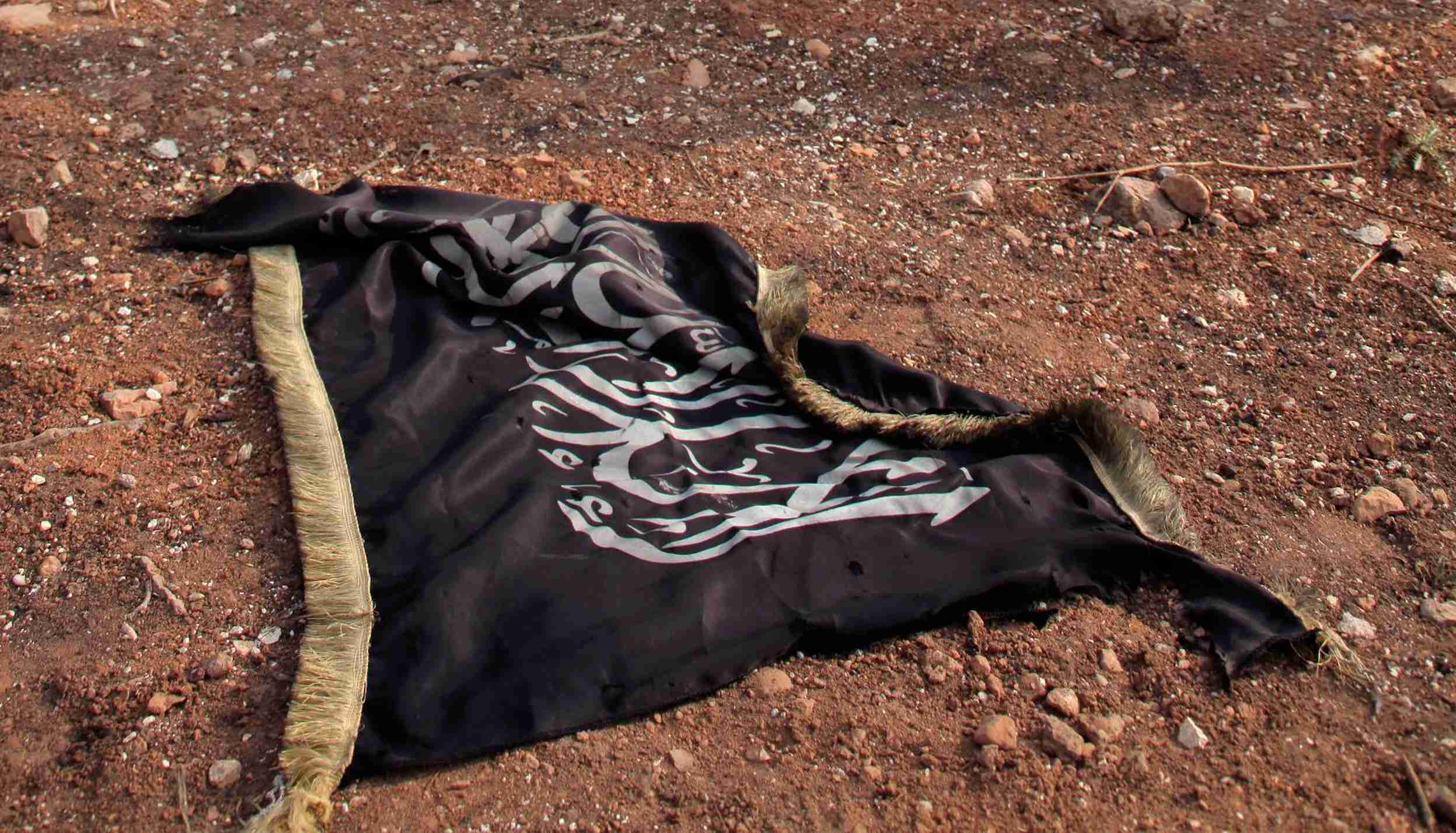 An Islamist flag is seen on the ground near the main highway leading Aleppo to Raqqa November 11, 2013. REUTERS/George Ourfalian (SYRIA - Tags: POLITICS CIVIL UNREST) - GM1E9BB1PZB01