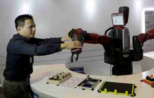 A staff member sets up the position of a mechanical hand for a Baxter robot of Rethink Robotics, during a display at the World Economic Forum (WEF), in China's port city Dalian, Liaoning province, China, September 9, 2015. Chinese robotics firms are grappling with a weakening economy and slumping automotive sector, and industry insiders already predict a market bubble just three years after the central government issued policies to spur robotics development. Picture taken September 9, 2015. REUTERS/Jason Lee  - GF10000208986