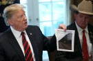 "U.S. President Donald Trump shows a photo of a ""typical"" border wall design  during a ""roundtable discussion on border security and safe communities"" with state, local, and community leaders in the Cabinet Room of the White House in Washington, U.S., January 11, 2019. REUTERS/Leah Millis - RC1B9D0904A0"
