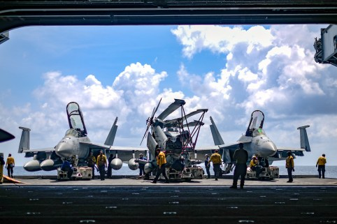 U.S. Navy sailors move aircraft from an elevator into the hangar bay of the aircraft carrier USS Theodore Roosevelt in the South China Sea April 8, 2018. Picture taken April 8, 2018. U.S. Navy/Mass Communication Specialist Seaman Michael Hogan/Handout via REUTERS.  ATTENTION EDITORS - THIS IMAGE WAS PROVIDED BY A THIRD PARTY - RC19F1104180