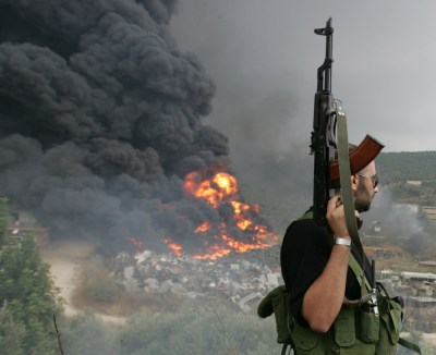 A Lebanese Hizbollah guerrilla looks at a fire rising from a burning object in a Beirut suburb July 17,2006. Israeli Defence Minister Amir Peretz said on Monday that no Israeli jet or helicopter had been shot down over Lebanon but did not rule out that a drone many have been downed. REUTERS/Issam Kobeisi (LEBANON) - GM1DTBLBLOAA