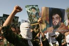 Demonstrators hold pictures of Lebanese Hezbollah leader Sayyed Hassan Nasrallah (R) and Iran's Supreme Leader Ayatollah Ali Khamenei (C) during Jerusalem Day demonstration in Tehran October 20, 2006. REUTERS/Caren Firouz (IRAN) - GM1DTTJIUTAA