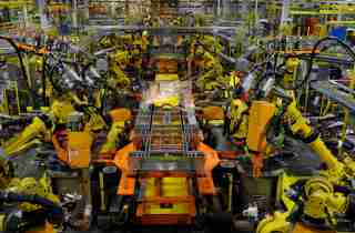 Robotic arms spot welds on the chassis of a Ford Transit Van under assembly at the Ford Claycomo Assembly Plant in Claycomo, Missouri April 30, 2014.  REUTERS/Dave Kaup  (UNITED STATES - Tags: BUSINESS TRANSPORT) - GM1EA510A6N01