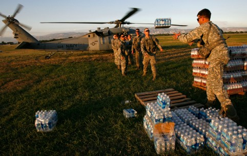U.S. soldiers of the 82nd Airborne help load water onto a Navy helicopter at a staging area at Port-au-Prince international airport January 17, 2010. Relief efforts continue in the island nation's capital after last week's devastating earthquake. U.S. troops will help U.N. peacekeepers keep order on Haiti's increasingly lawless streets, the country's president said on Sunday as aid workers struggled to get food and medical assistance to desperate earthquake survivors.      REUTERS/Hans Deryk    (HAITI - Tags: DISASTER MILITARY) - GM1E61I0YZK01