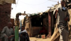 """Water drips from a tap as people sit in the Eshash el-Sudan slum in the Dokki neighbourhood of Giza, south of Cairo, Egypt September 2, 2015. Residents of the slum clashed with police in late August, when about 50 ramshackle huts were destroyed and at least 20 people were injured by teargas, local media reported, as authorities attempt to clear the area and rehouse residents. The slum dwellers, some of whom have called Eshash el-Sudan home for 50 years, say there are not enough apartments built nearby to house them. The residents of the slum eke out a living by disposing of rubbish or baking bread. Schooling is too expensive for most of their children, who play with salvaged rubbish amid shacks made out of discarded wood and leather. REUTERS/Amr Abdallah DalshSEARCH """"ESHASH EL-SUDAN"""" FOR ALL PICTURES  - GF10000200359"""