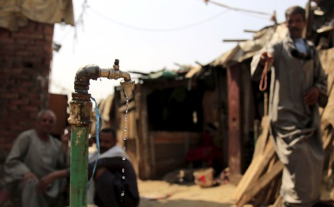 "Water drips from a tap as people sit in the Eshash el-Sudan slum in the Dokki neighbourhood of Giza, south of Cairo, Egypt September 2, 2015. Residents of the slum clashed with police in late August, when about 50 ramshackle huts were destroyed and at least 20 people were injured by teargas, local media reported, as authorities attempt to clear the area and rehouse residents. The slum dwellers, some of whom have called Eshash el-Sudan home for 50 years, say there are not enough apartments built nearby to house them. The residents of the slum eke out a living by disposing of rubbish or baking bread. Schooling is too expensive for most of their children, who play with salvaged rubbish amid shacks made out of discarded wood and leather. REUTERS/Amr Abdallah DalshSEARCH ""ESHASH EL-SUDAN"" FOR ALL PICTURES  - GF10000200359"