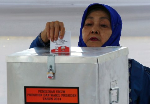 """A voter casts her ballot at a polling station, where Indonesian presidential candidate Joko """"Jokowi"""" Widodo and his wife Iriana, will cast their vote later in Jakarta July 9, 2014. Indonesians voted in a presidential election on Wednesday that has become a closely fought contest between the old guard who flourished under decades of autocratic rule and a new breed of politician that has emerged in the fledgling democracy.Only the third direct election for a president in the world's fourth-most populous state, the contest pits former special forces general Prabowo Subianto against Jakarta Governor Joko """"Jokowi"""" Widodo, who have been running neck-and-neck in opinion polls. REUTERS/Darren Whiteside (INDONESIA - Tags: ELECTIONS POLITICS) - GM1EA79192401"""