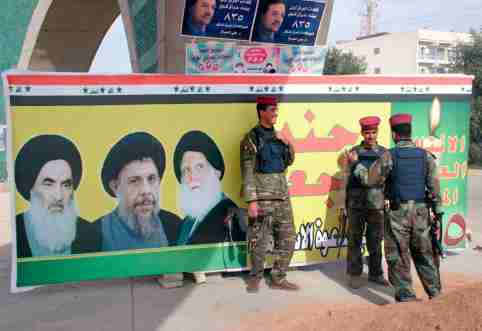 Iraqi soldiers stand guard near an election poster featuring pictures of Shi'ite leader Grand Ayatollah Ali Sistani (L), and slain clerics Ayatollah Mohammad Baqir al-Hakim (C) and Ayatollah Mohammad Sadeq al-Sadr in the holy city of Najaf December 6, 2005. Iraqis will go to the polls December 15 to elect their first full, four-year parliament since the fall of Saddam Hussein. REUTERS/Ali Abu Shish - RP2DSFIILWAB