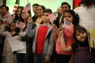 Children say the pledge of allegiance during a ceremony to present citizenship certificates to young people who earned citizenship through their parents, in Los Angeles, California, U.S., May 31, 2017. REUTERS/Lucy Nicholson - RC1E23D956B0