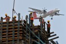 Construction workers erect scaffolding at the site of metro station as a SpiceJet Airlines aircraft flies past in the southern Indian city of Chennai May 14, 2012. Growth in Asia's third-largest economy is slowing as costlier credit and the impact of Europe's debt crisis on exports have sapped expansion. Gross domestic product rose 6.1 percent in December quarter from a year earlier, the slowest pace in near three years. REUTERS/Babu (INDIA - Tags: TRANSPORT BUSINESS CONSTRUCTION) - GM1E85E1KU101