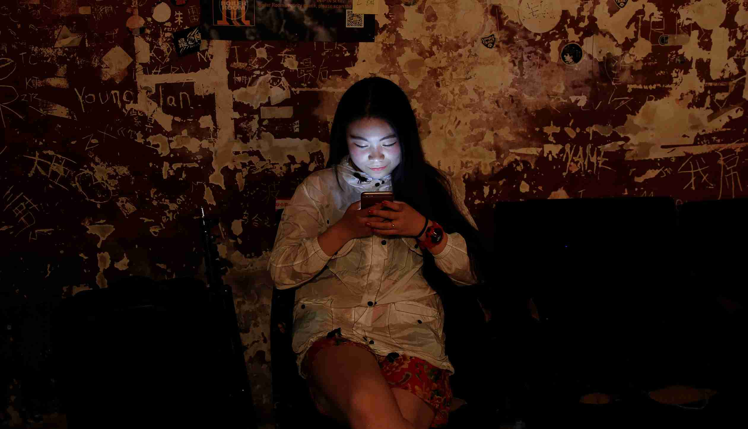"A girl uses her phone at Mao Live House during its last public concert night in central Beijing, China April 24, 2016. Mao Live House, a prominent live rock music venue in Beijing, shut its doors on the weekend, the latest closure to hit China's rock music scene. Owner Li Chi said the club, popular among fans of punk, metal and alternative rock since it opened nine years ago, was forced to close due to tighter rules on live performances. REUTERS/Damir Sagolj      SEARCH ""MAO LIVE"" FOR THIS STORY. SEARCH ""THE WIDER IMAGE"" FOR ALL STORIES  - S1BETBXEYAAB"