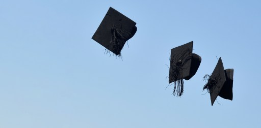 'Mortar board' hats are thrown in the air following a graduation ceremony for students at University of Brighton in Brighton, southern Britain, August 3, 2018. REUTERS/Toby Melville - RC17F2A09540