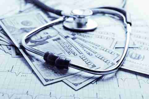 Dollars with stethoscope on them. Costs for the medical insurance. Blue toned