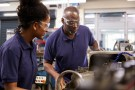 Engineer Showing Female Teenage Apprentice How To Use Lathe