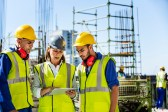 Male and female architects using digital tablet at construction site
