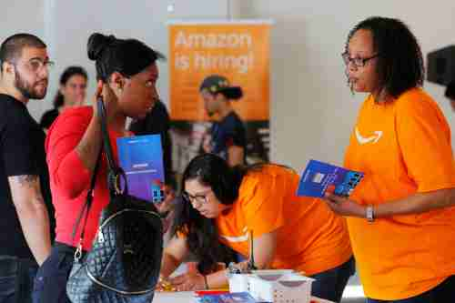 "Potential job applicants register for ""Amazon Jobs Day,"" a job fair being held at 10 fulfillment centers across the United States aimed at filling more than 50,000 jobs, at the Amazon.com Fulfillment Center in Fall River, Massachusetts, U.S., August 2, 2017. REUTERS/Brian Snyder - RC19CB5C0CE0"