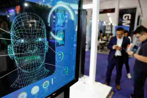 Visitors check their phones behind the screen advertising facial recognition software during Global Mobile Internet Conference (GMIC) at the National Convention in Beijing, China April 27, 2018. REUTERS/Damir Sagolj - RC1838EC3EA0