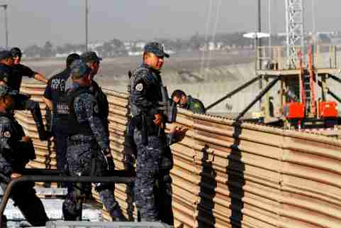 Mexican federal police officers look over the current border fence, while U.S. border patrol authorities (not pictured) visit the site where several prototypes for U.S. President Donald Trump's border wall with Mexico have been built, in this picture taken from the Mexican side of the border, in Tijuana, Mexico, October 26, 2017. REUTERS/Jorge Duenes - RC1DEABF0E80