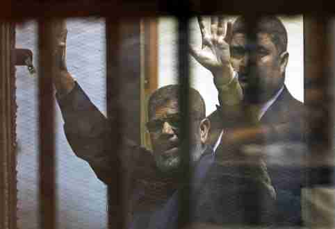 Deposed Egyptian President Mohamed Mursi greets his lawyers and people from behind bars after his verdict at a court on the outskirts of Cairo, Egypt June 16, 2015. An Egyptian court sentenced deposed President Mohamed Mursi to death on Tuesday on charges of killing, kidnapping and other offences during a 2011 mass jail break.The general guide of the Muslim Brotherhood, Mohamed Badie, and four other Brotherhood leaders were also handed the death penalty. More than 80 others were sentenced to death in absentia. REUTERS/Asmaa Waguih      TPX IMAGES OF THE DAY      - GF10000129302