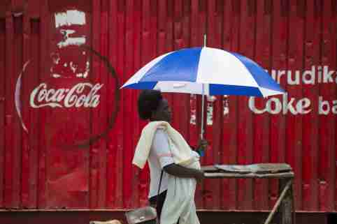 A woman walks by a store decorated with a Coca-Cola logo in the town of Ahero near Kisumu, Kenya April 20, 2017. REUTERS/Baz Ratner - RC1E52E26840