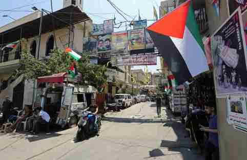 A boy rides on a motorbike as he drives past Palestinian flags at Burj al-Barajneh refugee camp in Beirut, Lebanon, June 24, 2019.  REUTERS/Aziz Taher - RC1896B964D0