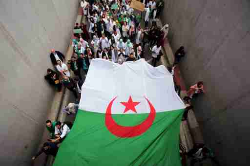 Health workers carry a national flag as they march during a protest calling on President Abdelaziz Bouteflika to quit, in Algiers, Algeria March 19, 2019. REUTERS/Ramzi Boudina TPX IMAGES OF THE DAY - RC16969E1C30