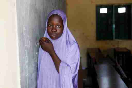 A girl wearing hijab stands in a classroom Hausari primary school  in Michika village, northeast Nigeria June 12, 2017. Picture taken June 12, 2017. REUTERS/Akintunde Akinleye - RC1828EAF0C0