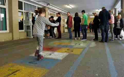 A girl plays hopscotch as people line up to vote in the first round of 2017 French presidential election at a polling station in Marseille, France, April 23, 2017. REUTERS/Philippe Laurenson     TPX IMAGES OF THE DAY - RC1DF78E8BB0