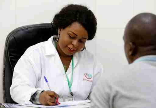 Dr. Christelle Azier-Pohoun of BIO-MEDICAL, a center that provides medical visits for people who pass the driver's license, speaks to a patient during a consultation in Abidjan, March 28, 2019. REUTERS/Thierry Gouegnon. - RC1BC64E9F30