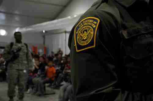 A Customs and Border Patrol officer stands near migrants at the Donna Soft-Sided Processing Facility in Donna, Texas, U.S. July 12, 2019. Picture taken July 12, 2019. REUTERS/Veronica G. Cardenas - RC15F00ADDE0