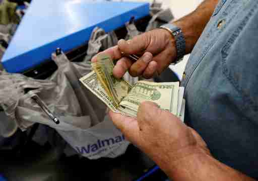 FILE PHOTO: A customer counts his cash at the checkout lane of a Walmart store in the Porter Ranch section of Los Angeles November 26, 2013.   REUTERS/Kevork Djansezian/File Photo          GLOBAL BUSINESS WEEK AHEAD PACKAGE Ð SEARCH BUSINESS WEEK AHEAD MARCH 13 FOR ALL IMAGES - RC1E3B0702B0