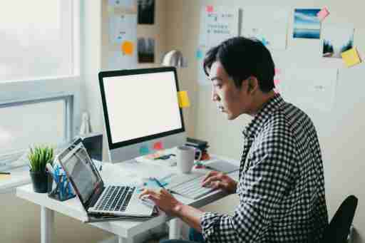 Man looking at laptop while working from his small office.