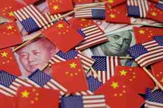 FILE PHOTO: A U.S. dollar banknote featuring American founding father Benjamin Franklin and a China's yuan banknote featuring late Chinese chairman Mao Zedong are seen among U.S. and Chinese flags in this illustration picture taken May 20, 2019. REUTERS/Jason Lee/File Photo - RC1965288CA0