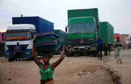 A woman hawks merchandise past transit trucks at Mpondwe border that separates Uganda and the Democratic Republic of Congo, in Mpondwe, Uganda, June 14, 2019. REUTERS/James Akena - RC1ADF153830