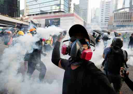 An anti-government protester throws back a tear gas canister at the police during a demonstration near Central Government Complex in Hong Kong, China, September 15, 2019. REUTERS/Jorge Silva - RC14CEE90590