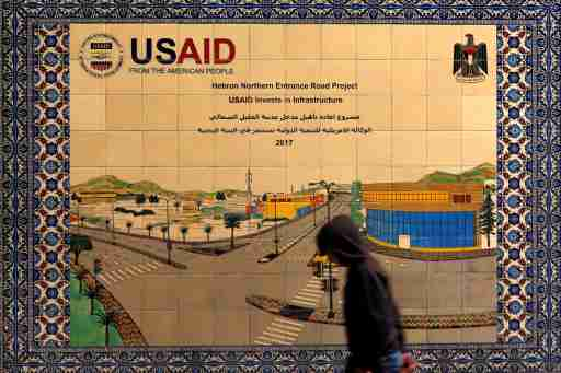 A Palestinian walks past a ceramic sign of a U.S. Agency for International Development (USAID) project in Hebron in the Israeli-occupied West Bank January 31, 2019. Picture taken January 31, 2019. REUTERS/Mussa Qawasma - RC1DBE2B9C60