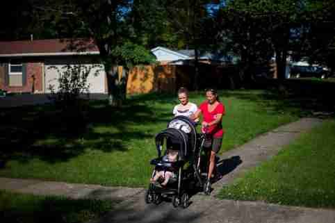 Heather Padgett, with her mother Debi Padgett (R), takes her daughters Kinsley and Kiley for a walk outside their home in Cincinnati, Ohio July 16, 2015. Until she got clean last August, Heather was part of what the Centers for Disease Control has called a heroin epidemic - a 100 percent rise in heroin addiction among Americans between 2002 and 2013. The sharp rise in heroin addiction, coupled with the risks of newborns developing withdrawal symptoms after they are sent home, has led a group of Cincinnati hospitals to try what they say is the first program of its kind in the United States: testing all mothers, or their infants, for opiates regardless of background, not just those who seem high-risk. To match Feature USA-HEROIN/MATERNALTESTING  Picture taken July 16, 2015.  REUTERS/Aaron P. Bernstein - GF20000015645