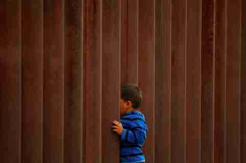 """A child peeks through the border fence during the """"Interfaith Service for Justice and Mercy at the Border"""" to demand the U.S. government to end the separation of immigrant children from their parents at the border, in Ciudad Juarez, Mexico September 7, 2018. REUTERS/Jose Luis Gonzalez - RC1410DF6D00"""