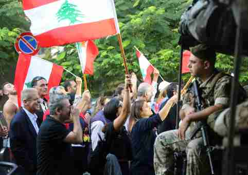 Demonstrators wave Lebanese flags as the pass by Lebanese soldiers during a protest in Beirut, Lebanon, October 31, 2019. REUTERS/Goran Tomasevic - RC116FDD2CA0