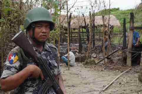 A Myanmar border guard police officer stands guard in front of the remains of a house burned down in a clash between suspected militants and security forces in Tin May village,  Buthidaung township, northern Rakhine state, Myanmar July 14, 2017. Picture taken July 14, 2017. REUTERS/Simon Lewis - RC17166738A0