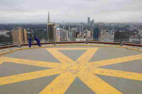 Men look at the Nairobi skyline from observation point on the top of the Kenyatta International Convention Centre in Nairobi, Kenya, June 21, 2019. REUTERS/Baz Ratner - RC1D930C2460