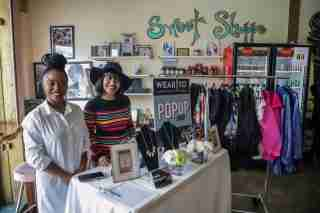 Ashleigh Burden and Quen Carter, of Wear To, clothing curated for the modern woman's agenda, sales items from the online store during the Detroit Black Business Crawl at Good Cakes and Bakes vendor market on the Livernois Avenue of Fashion in Detroit on Small Business Saturday, Nov. 30, 2019.Smallbizsat 113019 Kpm 389