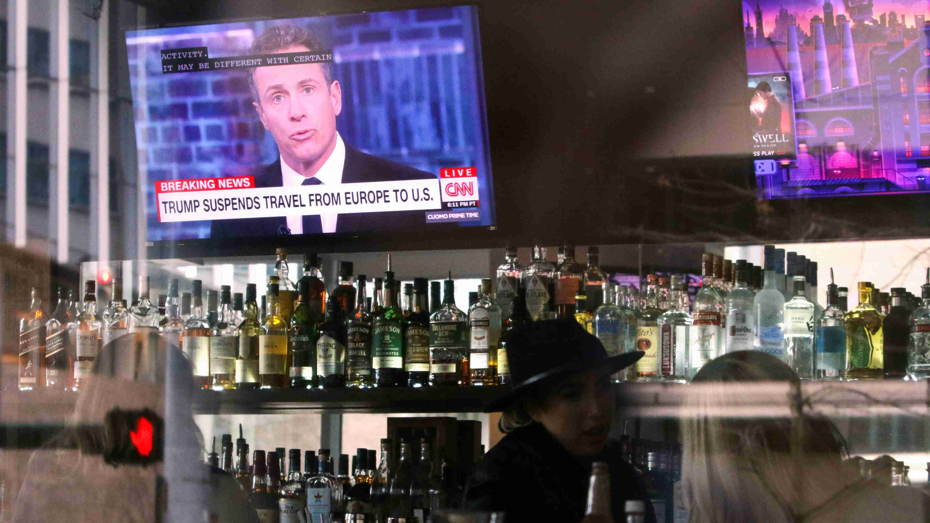 """A CNN headline reading """"Trump Suspends Travel From Europe to U.S."""" is pictured on the television in the bar at A Pizza Mart, in Seattle, Washington, U.S. March 11, 2020. REUTERS/Jason Redmond"""