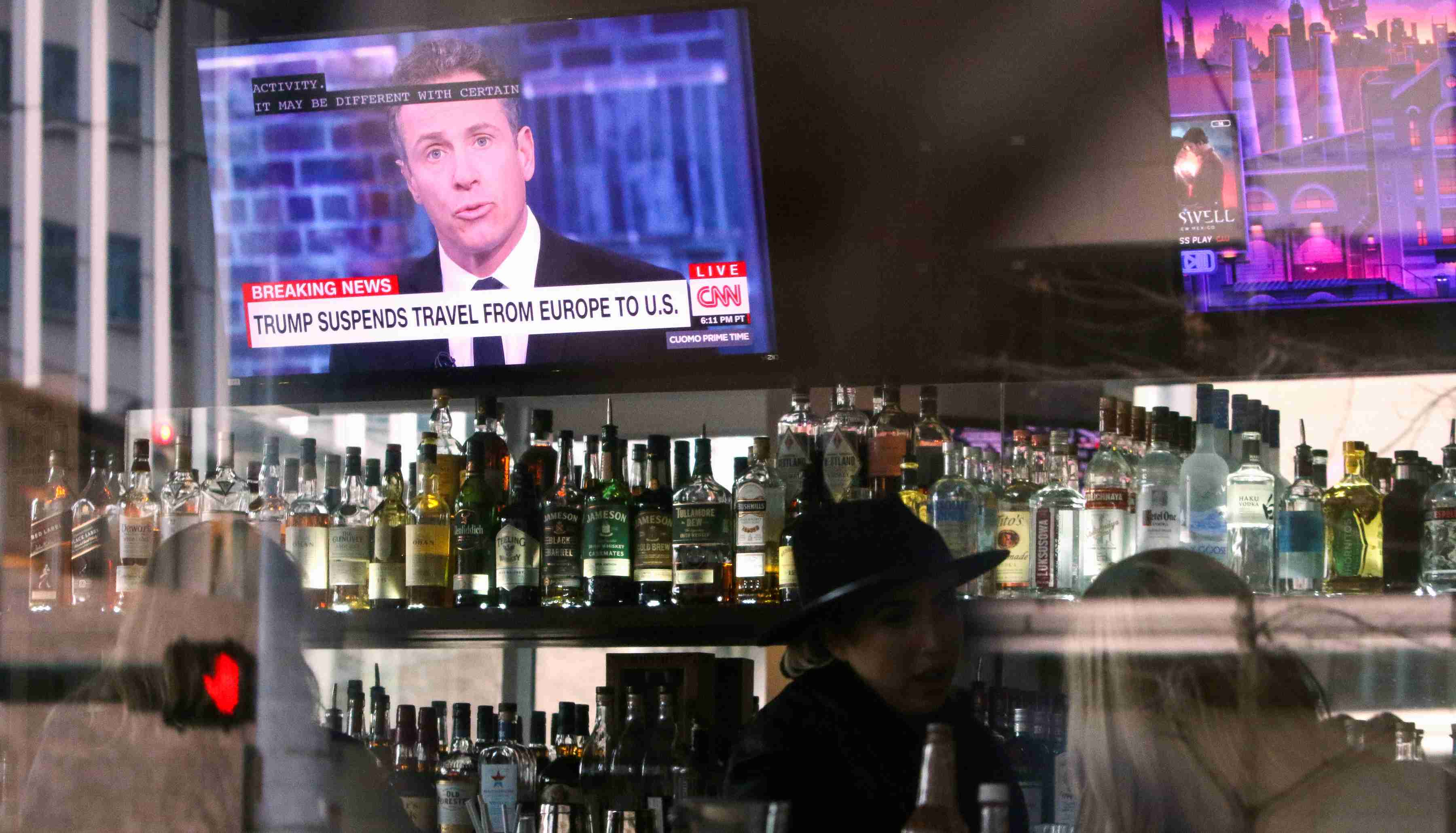 "A CNN headline reading ""Trump Suspends Travel From Europe to U.S."" is pictured on the television in the bar at A Pizza Mart, in Seattle, Washington, U.S. March 11, 2020. REUTERS/Jason Redmond"