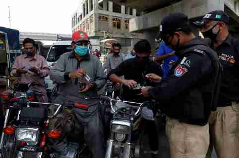 Police officers check identity cards of commuters before letting them cross a checkpoint during a partial lockdown after Pakistan shut all markets, public places and discouraged large gatherings amid an outbreak of coronavirus disease (COVID-19), in Karachi, Pakistan, March 24, 2020. REUTERS/Akhtar Soomro