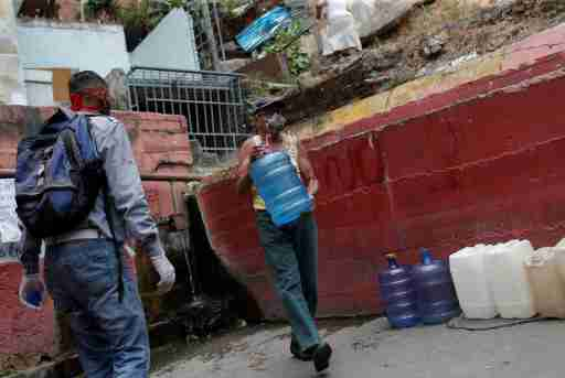 An elder carry a plastic container filled with water from a pipe in a street of a slum during a nationwide quarantine due to coronavirus disease (COVID-19) outbreak in Caracas, Venezuela April 2, 2020. Picture taken April 2, 2020. REUTERS/Manaure Quintero