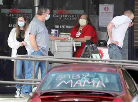 Visitors leave the screening station for coronavirus in front of the emergency department entrance at Cartersville Medical Center required for hospital entry on Tuesday, March 17, 2020, in Cartersville, Ga., where several patients have been confirmed to have COVID-19 and dozens of others are under investigation who are suspected to potentially have the coronavirus. Two triage tents have been set up for anyone who has symptoms. (Curtis Compton/Atlanta Journal-Constitution/TNS)
